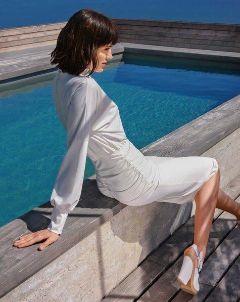 Burda 110 08/2017 model photo. A woman in a white dress sits beside a swimming pool