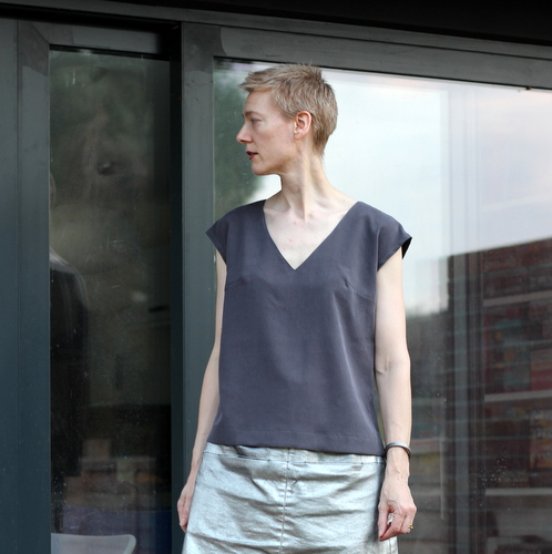 A woman wearing a grey top Burda 106b 06/2011 stands in front of a window