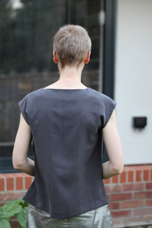 A woman wearing a grey top Burda 106b 06/2011 stands with her back to the viewer
