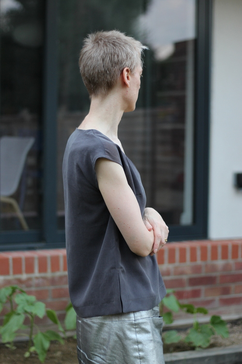 A woman wearinf a grey top Burda 106b 06/2011 stands side on