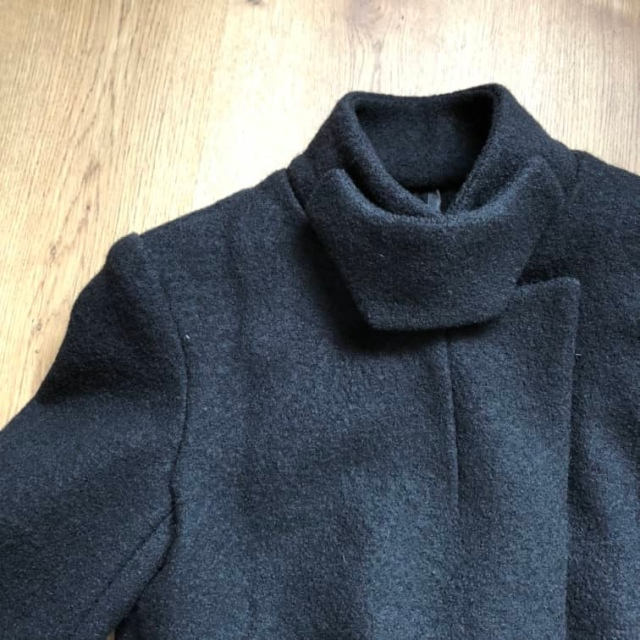 A closeup of the necline of a high necked black wool jacket (Vogue 1466)