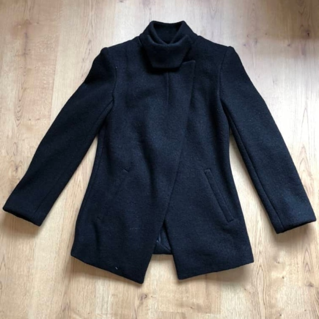 A black wool jacket (Vogue 1466) with a high neckline lies on the floor