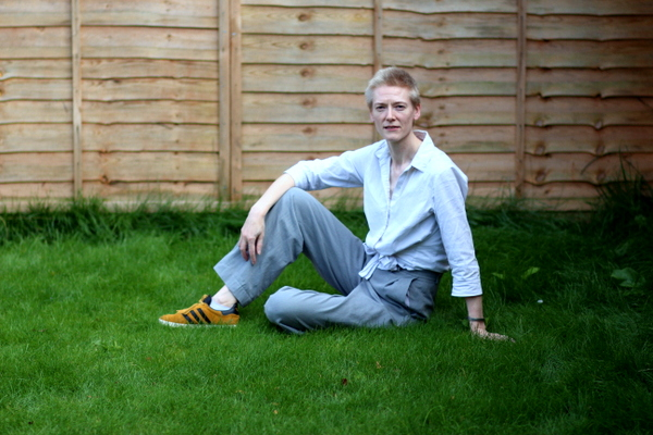 A woman in grey trousers and a white shirt sits on grass