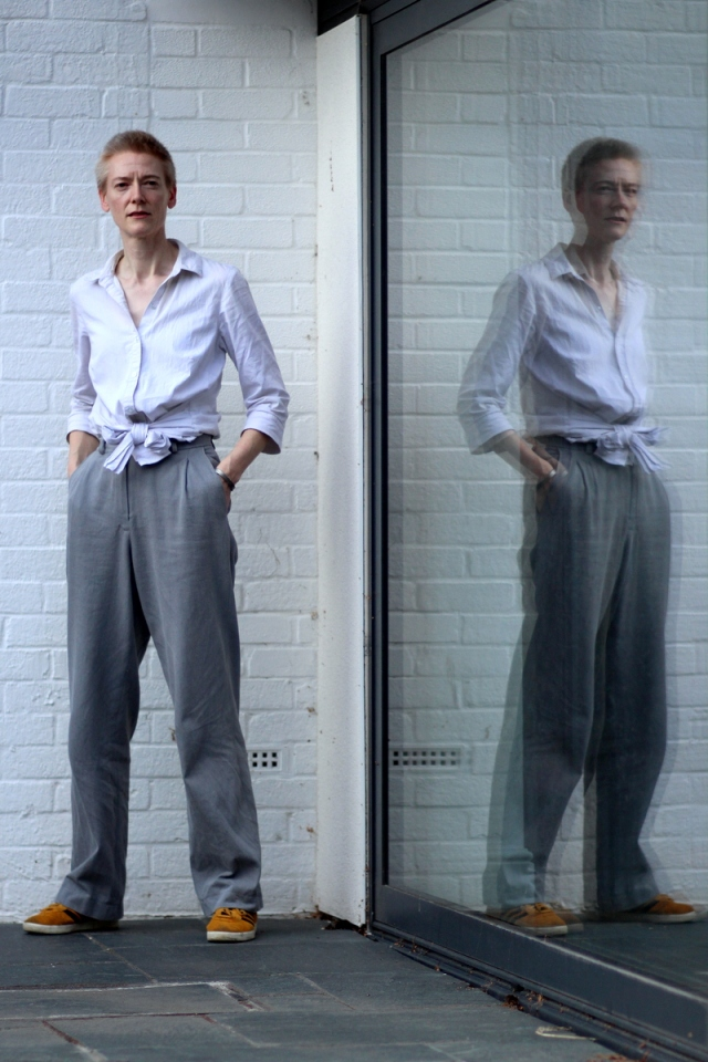 A woman in grey trousers and white shirt stands by a window