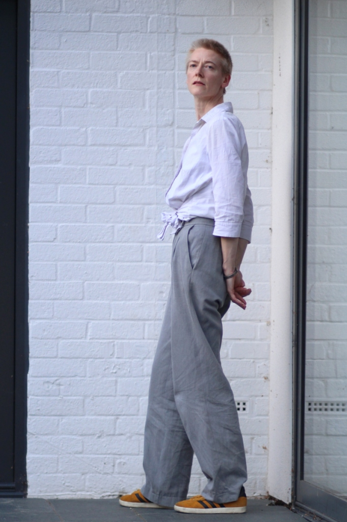 A woman in grey trousers and white shirt stands by a white wall