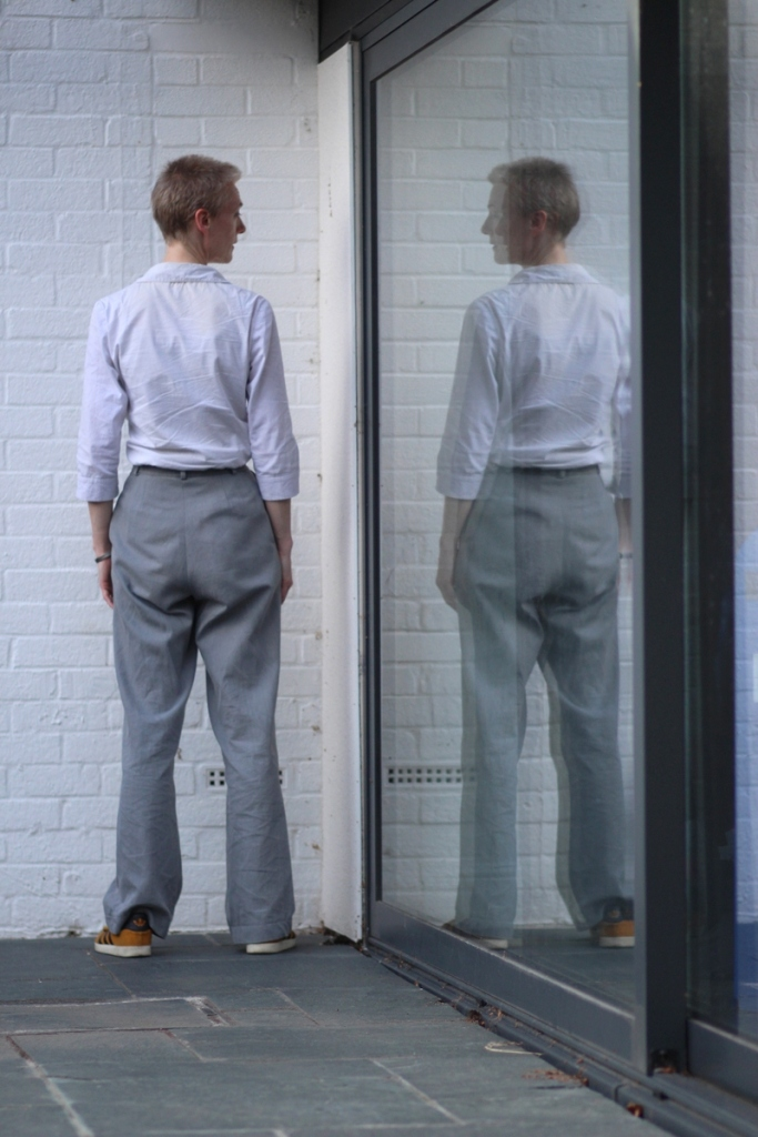 A woman in grey trousers and white shirt stands by a window with her back to the camera