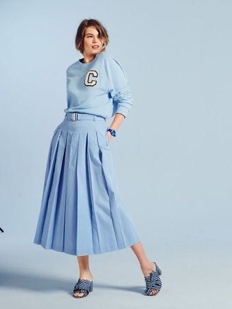 Woman in pale blue pleated culottes and letter jersey
