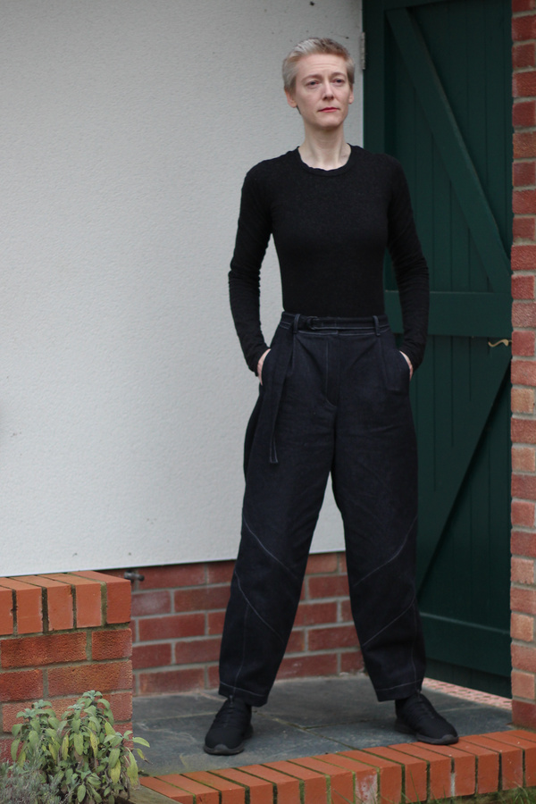 A woman wearing black cocoon trousers and a black t shirt stands in a garden
