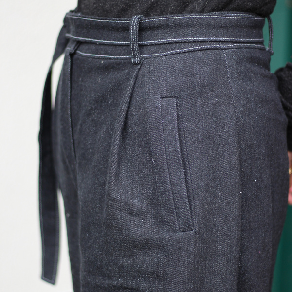 Closeup of black denim trousers with welt pockets, self belt, and pleats