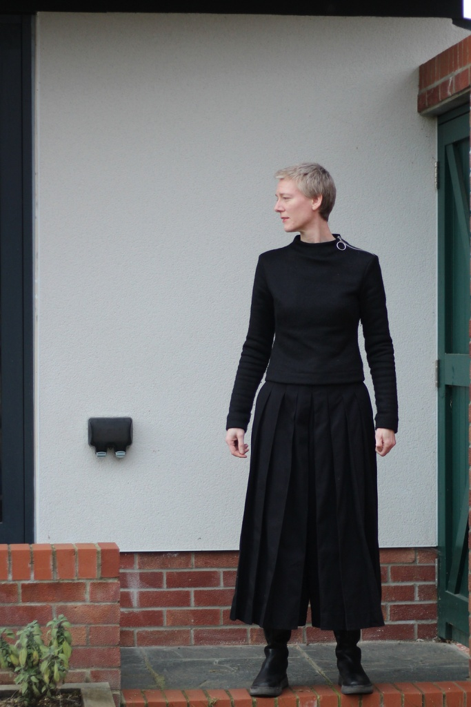 A woman in a black jumper and black pleated culottes