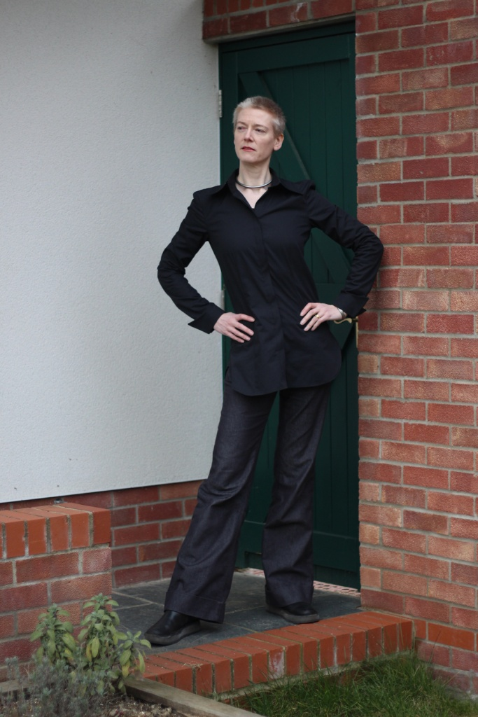 A woman wearing a black blouse and jeans standing in front of a green door