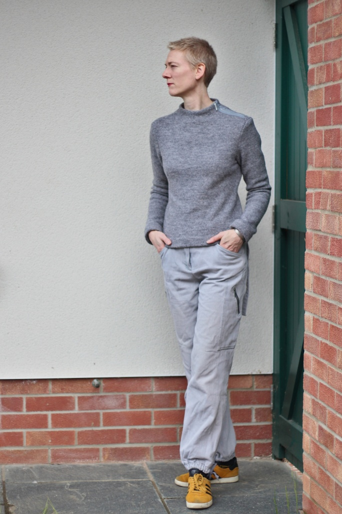 A woman with short hair wearing a grey jumper and cargo trousers , and yellow trainers