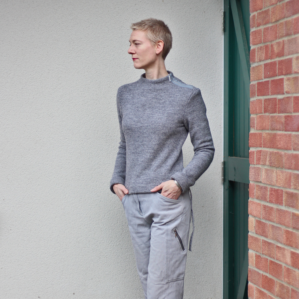 A woman  in a grey jumper and trousers