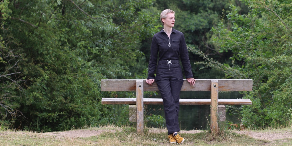 A woman in a black jumpsuit and yellow trainers leans against a bench