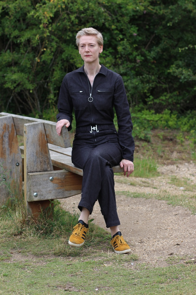 A woman in a black jumpsuit and yellow trainers sits on a bench