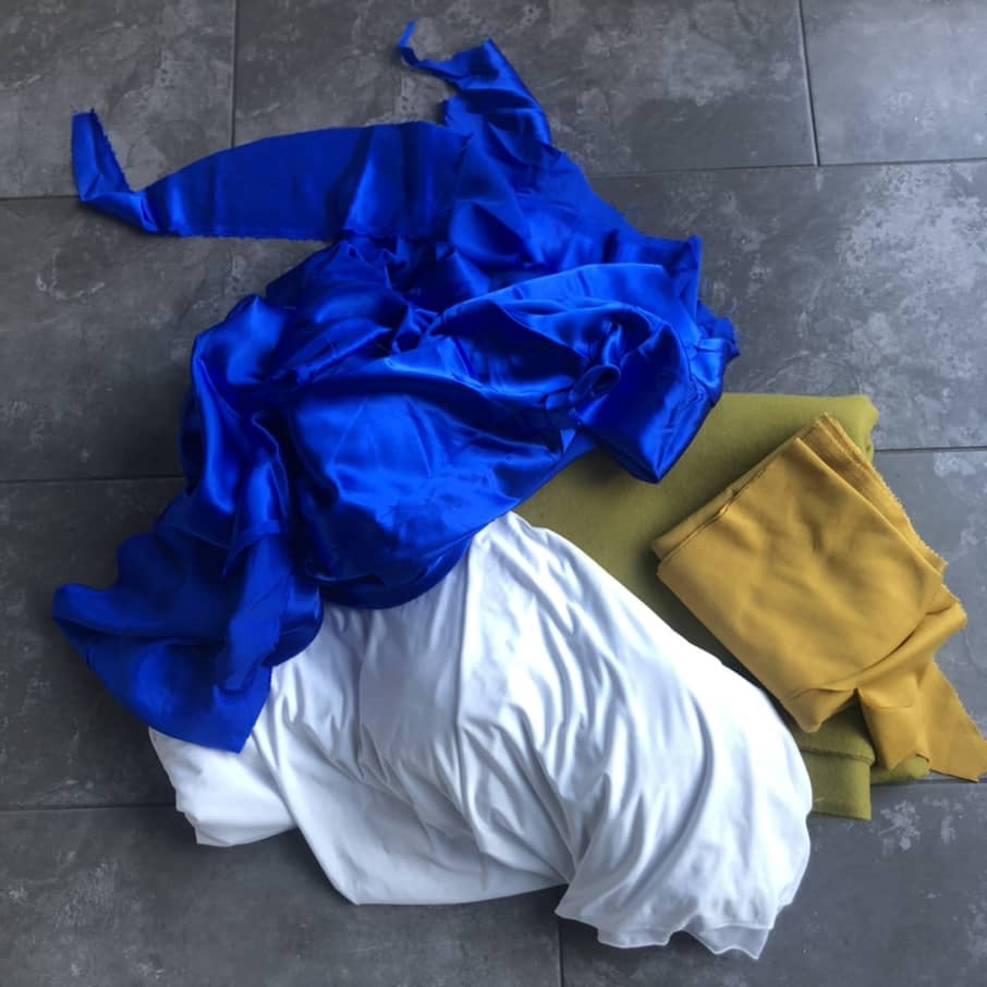 Blue, yellow, green and white fabrics on a grey tile floor